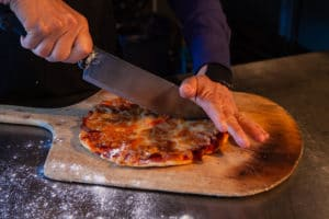 chef, using a large knife to slice a thin stonebaked pizza on a rustic wooden board at a Bainbridge Island Restaurants