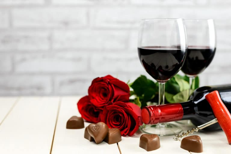 Valentine's Day at a Bainbridge Island Winery Two glasses of wine, wine bottle, corkscrew, red roses and chocolate hearts on a white wooden table.